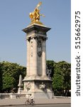 Small photo of PARIS, FRANCE - JUNE 05, 2008: Woman on a bicycle, passing next to one of the columns with golden sculptures, to cross the bridge of Alexander III