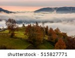 red hot sunrise with cold morning fog in rural valley with high mountains. green grass and trees with colorful foliage on the hillside meadow - stock photo