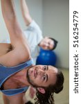 Small photo of Portrait of man doing aerobic exercise in fitness studio