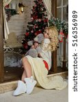 Small photo of Girl sitting on a veranda threshold, which is decorated Christmas fir tree. gently hugs a teddy bear. The legs which are covered by a white blanket Volgograd region, Russia, November 8, 2015