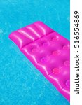 Small photo of Pink air mattress on a swimming pool - holiday tropical background concept