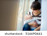 mother sitting on a window sill ... | Shutterstock . vector #516690661