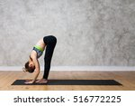 Small photo of Young woman practicing Standing forward bend, Uttanasana yoga pose against texturized wall / urban background