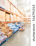 Small photo of Blurred image row of aisles, bins and shelves from floor to ceiling with flatbed cart in large warehouse. Defocused background industrial distribution storehouse interior aisle, hypermarket, wholesale