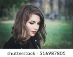 Small photo of Lovely Girl in the Park. Pretty Woman with Long Bob Hairstyle