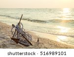 Rusty anchor wet beach sand and ...