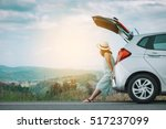 Small photo of Woman traveler sitting on hatchback car with mountain background in vintage tone