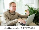 happy adult man sitting at home ...   Shutterstock . vector #517296685