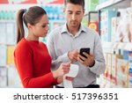 couple doing grocery shopping... | Shutterstock . vector #517396351