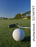 golf ball and putter near green and flag - stock photo