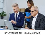 Three Workers At Desk Using...