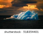 Small photo of Dangerous and alluring Arctic. Terrible and magnificent iceberg in polar ocean of blue ice, similar to one that sunk Titanic.
