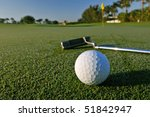 golf ball and putter near flag, with dew on grass, focus on ball - stock photo