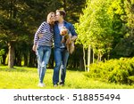 Stock photo lifestyle happy couple of two walk on a sunny day in the park with a dog 518855494