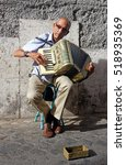 Small photo of Rome, Italy - August 16, 2016: Street musician playing accordion to earn some money from tourists in Trastevere district in Rome. Street musicians are one of the attractions of Rome.