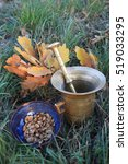Small photo of The individual steps of preparing acorn coffee. Roasted acorns in a ceramic bowl and mortar tin, which were shattering. Mortar cup and autumn leaves of oak.