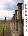 Small photo of outdoor numerous ancient broken doric columns by the greenish grass field in the open museum of Pompeii, Italy in perspective view under a summer cloudy grey sky with nobody presents in this frame.