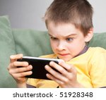 Young Boy Playing Handheld Gam...
