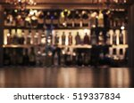 Stock photo empty wooden bar counter with defocused background of restaurant bar or cafeteria and copy space 519337834