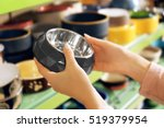 Stock photo hands of young woman selecting bowl in pet shop close up view 519379954