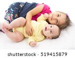 Little Sisters Laying On Bed, Isolated On White Background - stock photo