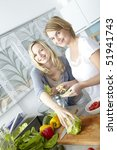 two women cook in kitchen