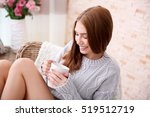 Small photo of Beautiful girl with hot drink relaxing at home