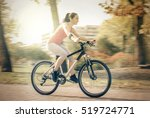 carefree woman riding bicycle... | Shutterstock . vector #519724771