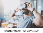 Stock photo bearded young man wearing virtual reality goggles in modern coworking studio smartphone using with 519893869