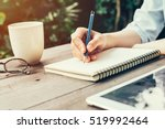 Stock photo woman hand with pencil writing on notebook at coffee shop woman working in outdoor at coffee shop 519992464