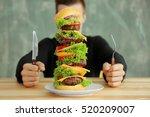 man eating huge burger at table | Shutterstock . vector #520209007