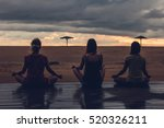 three silhouettes meditating at ... | Shutterstock . vector #520326211
