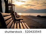 Stock photo lake garda italy a tranquil sunset view of benches looking over lake garda italy towards the 520433545