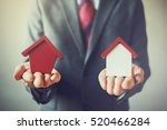 businessman holding two houses... | Shutterstock . vector #520466284