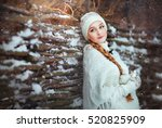 Small photo of Beautiful girl with long blonde braid and knitted hat standing near wooden fence and looking afar. Winter magic day.