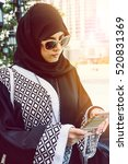 Small photo of Portrait of Arab woman. Arab woman wearing hijab reading a message on a cell phone against the backdrop of the skyscrapers of Dubai. The woman is dressed in a black abaya