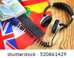 Small photo of language course headphone and flag on wooden table