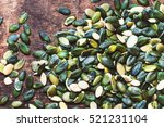 pumpkin seeds over wooden... | Shutterstock . vector #521231104