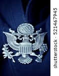 Small photo of U.S. Official Pin (American Eagle) on a navy blue uniform.