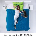 Stock photo young happy woman relaxing on the bed at home she is listening to music with her tablet and 521730814
