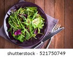Small photo of Fresh salad plate with mixed greens (arugula, mesclun, mache) on dark wooden background top view. Healthy food. Green meal.