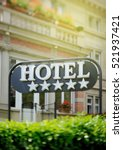 """Small photo of Detail of a luxury five stars hotel with beautiful building in the background on a beautiful sunny day. Tilt shift lens used to accent the word """"hotel"""" and to emphasize the background"""