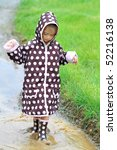 Little girl walking through a mud puddle in her rain coat and boots. - stock photo