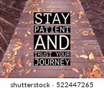 "Small photo of Inspirational motivational quote ""stay patient and trust your journey"" on wooden walkway with autumn leaves background."
