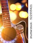 Small photo of Acoustic guitar and microphone with lights in the background. Country or bluegrass concert concept. Front view. Horizontal composition.