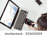 Small photo of Stock exchange market trading graph over the screen of telephone laptop on hand the trading graph background, business marketing trade concept