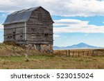 Old barn with rock foundation near the Canada, US border, with the Sweet Grass hills in the distant background - stock photo