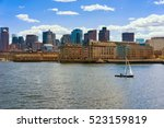 Small photo of Lonely sailboat floating across the river Charles in front of the skyline of Boston, USA. The city is one of the oldest in the United States. It was founded in 1630 by Puritan immigrants.