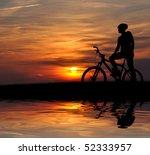 Small photo of mountain biker silhouette in sunrise