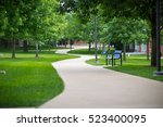 Pathway In A Lush Green Park.